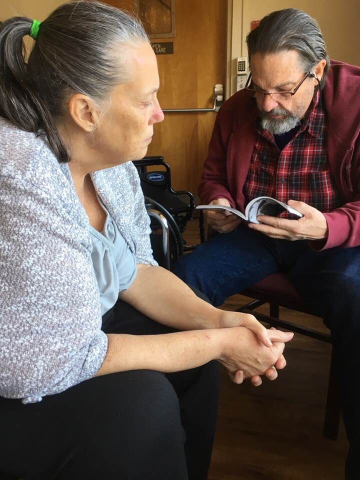 Dad reading to Mom at nursing home